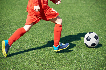 Child soccer player and ball on the football field