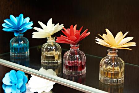 Flowers in jars with fragrant oils on dark