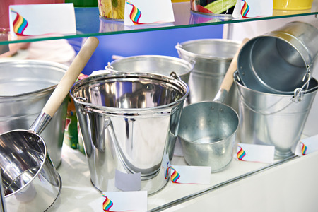 Metal galvanized buckets and kovshs on the counter in the store
