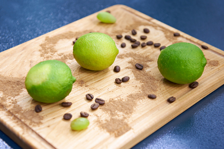 Green limes and coffee beans on a wooden cutting board
