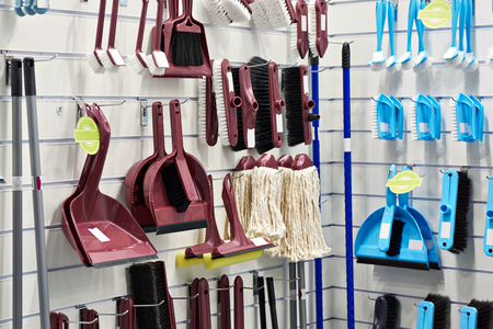 Plastic household brushes, scoops and mops in the hardware store Фото со стока
