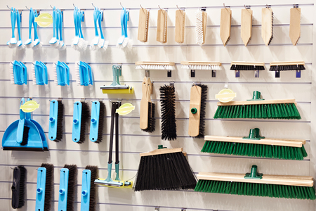 Plastic and wooden household brushes, scoops and mops in the hardware store