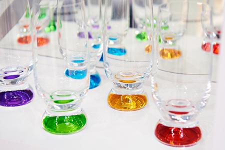Glasses of colored glass on white Фото со стока
