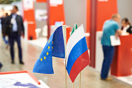 Flags of Russia and the European Union on the table of the exhibition Фото со стока