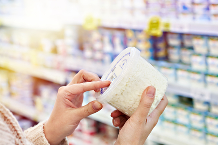 Buyer hands with plastic container of cottage cheese in the grocery store