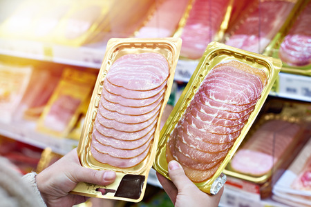 Woman chooses a slice of ham and meat  in vacuum package at the grocery store Stock fotó - 109912931