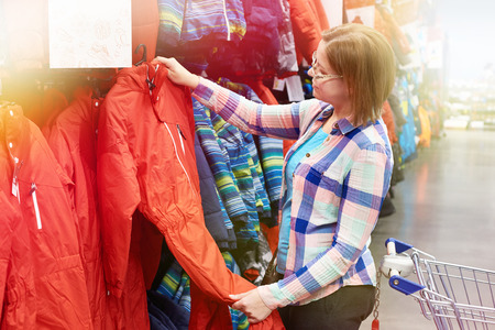 Woman chooses a ski jumpsuit in a sports store