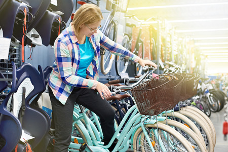 Woman chooses bicycle in sports store