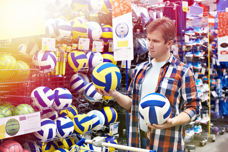 Man chooses volleyball in the sports shop