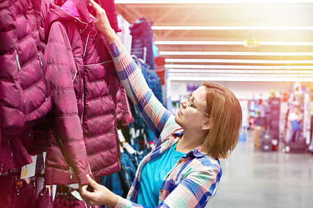Woman chooses a winter jacket in the store