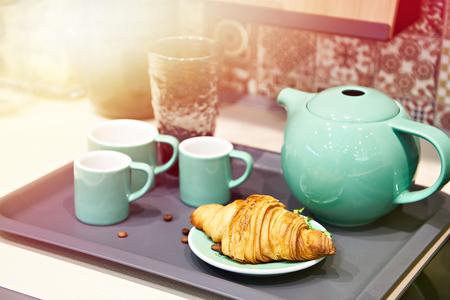 Croissant and coffee set on tray Фото со стока