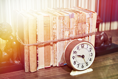 Old books tied up with rope on shelf and alarm clock