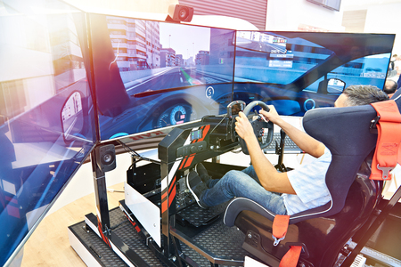 El hombre juega en un simulador de carreras de computadora