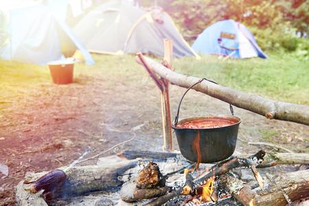 Bowler with a soup on a campfire and tourist tents Фото со стока