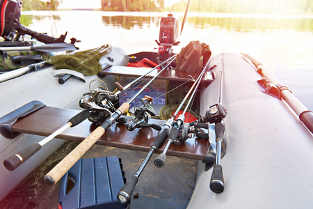 Fishing rods with spinning reels in a boat Фото со стока