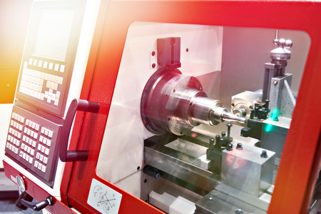 Modern lathe with CNC and workpiece Фото со стока