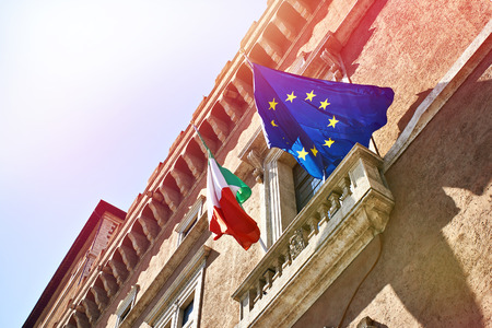 Flags of Italy and the European Union against the background of a clear blue sky