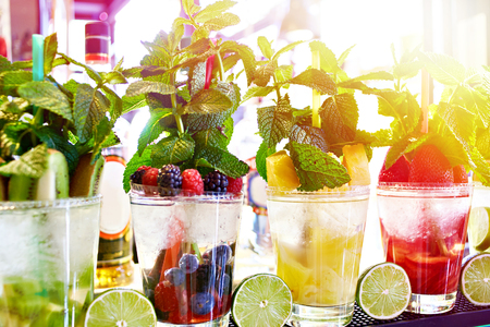 Fruit and berry cocktails with mint on the counter of a cafe Фото со стока