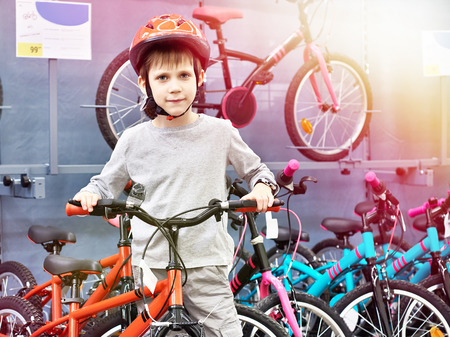 Boy in helmet chooses with bicycle in a sports supermarket