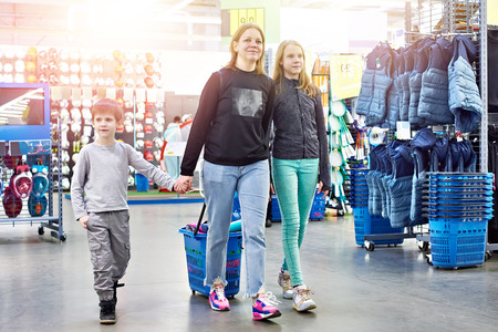 Family with a shopping cart in a sport goods store Фото со стока