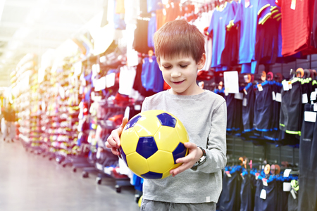 Boy with a soccer ball in a sports store