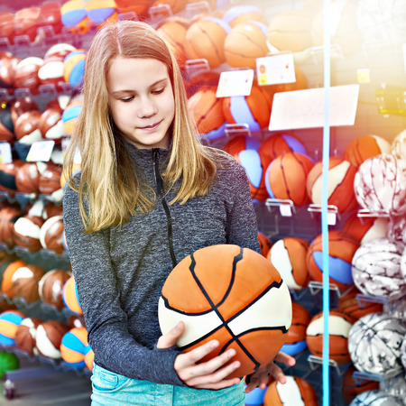 Girl with a basket ball in a sports store Фото со стока