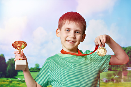 Boy sportsman winner with cup and medal on nature background