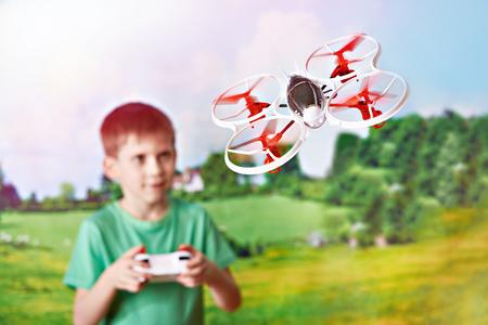 Little boy drives toy quadcopter drone at nature landscape Фото со стока