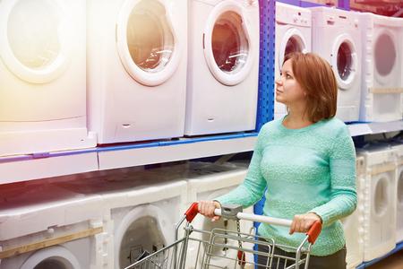 Woman housewife whit shopping cart shopping for washing machine, side view