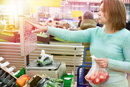 Woman weighing cucumbers and tomatoes in vegetable store