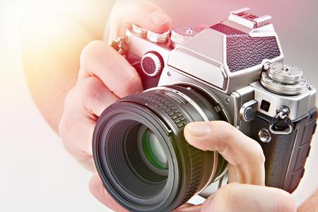Retro SLR camera in the hands of the photographer closeup Фото со стока