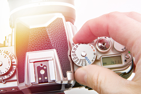 Photographer setting shutter control dial on retro SLR camera closeup
