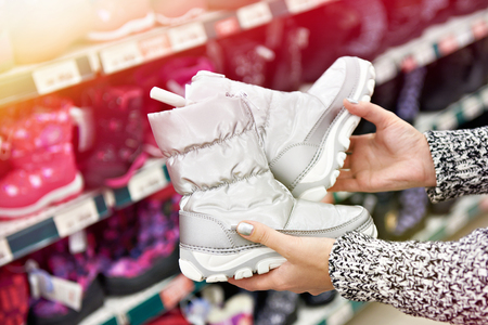 Winter boots in the hands of women customers in the store