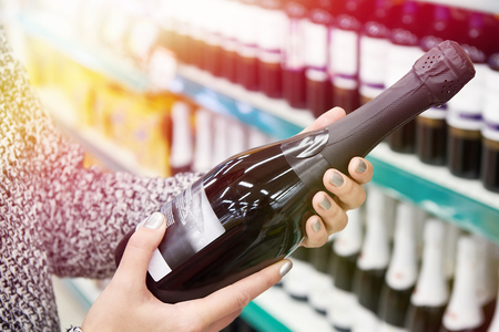 Woman with bottle of champagne in the store