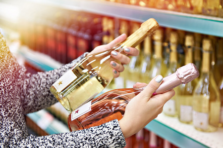 Woman with bottles of rose and white wine in the store Фото со стока