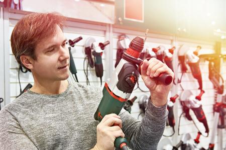 Man shopping for perforator in hardware store closeup Фото со стока
