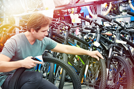 Man chooses the tire to the bike in the sports shop