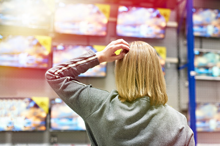 Buyer woman selects TV in store