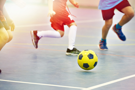 Dzieci grające w piłkę nożną z żółtą piłką nożną w pomieszczeniu