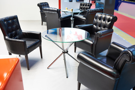 Glass table and black leather armchairs for negotiations Фото со стока