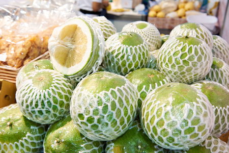 Pomelo fruits in the packaging on the market counter