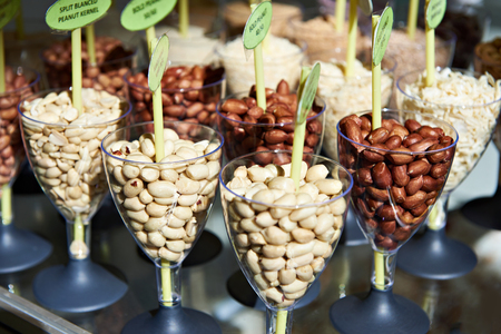 Different peanuts nuts in glass goblets on display in a store