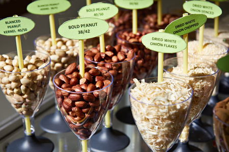 Different peanuts nuts and dried onion flakes in glass goblets