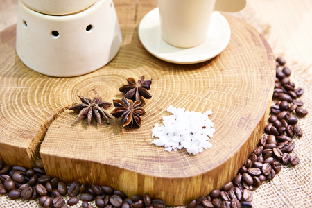 Still life with tea, coffe beans and cloves on wooden Фото со стока