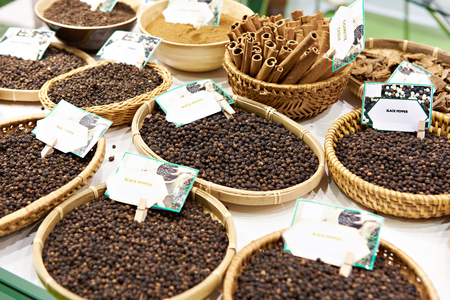 Black pepper in wooden plates on the market