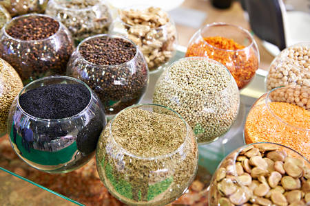 Seasoning black and white peppercorns and cumin in glass round jars in the store Фото со стока