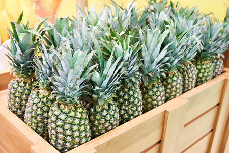 Pineapples in a wooden box in the store