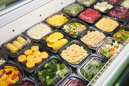 Chilled vegetables in plastic containers on the shop counter