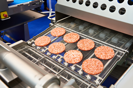 Pieces of minced meat on a conveyor belt machine wet breading Фото со стока
