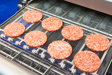 Pieces of minced meat on a conveyor belt machine wet breading 写真素材